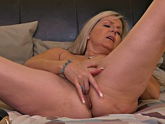 experienced mature woman rubs her pussy in bed