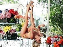 Blonde glamour girl munching on fruit outdoors