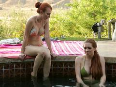 Two busty redhead beauties are licking each other and touching in the pool