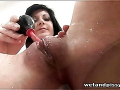 Brunette plays with a glass of piss